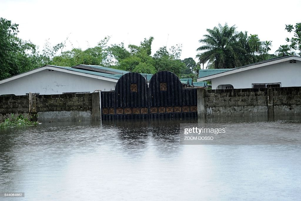 A flooded street is pictured in Monrovia on July 1, 2016 following heavy rains. Heavy rains have cut the only road access to Liberia's main airport, leaving travellers to cross some sections by canoe, passengers told AFP on July 1. At certain points the sole road between the capital Monrovia and Roberts International Airport is 1.5 metres (five feet) underwater. DOSSO