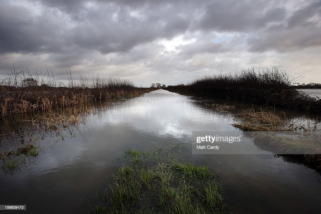 A flooded track passes fields covered in flood waters surrounding the village of Muchelney, which has been cut off by flooding on the Somerset Levels, on December 30, 2012 near Langport, England. The Met Office is warning of the risk of further flooding towards the end of the year, meaning 2012 is set to be the wettest on record.