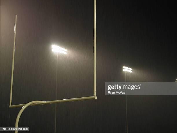 Floodlight illuminated at night, goal in foreground