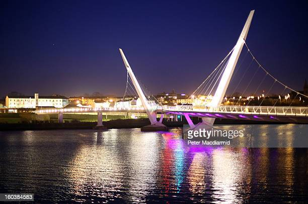 Floodlights illuminate the Peace Bridge on the River Foyle on January 30 2013 in Londonderry Northern Ireland A year of events have started as Derry...