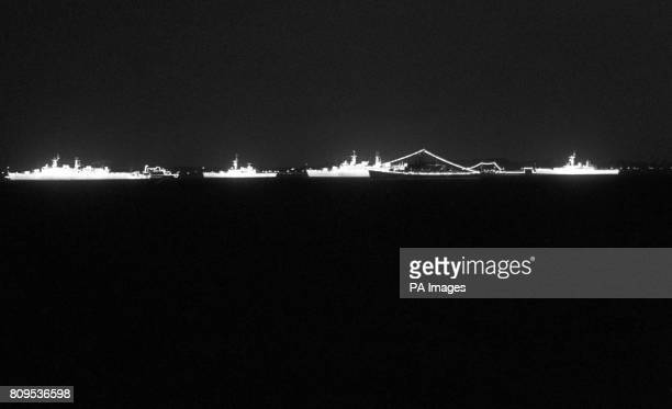 Floodlit Royal Navy ships make a frieze of glowing silhouettes on an inkdark sea They are part of the armada assembling at Spithead between the Isle...