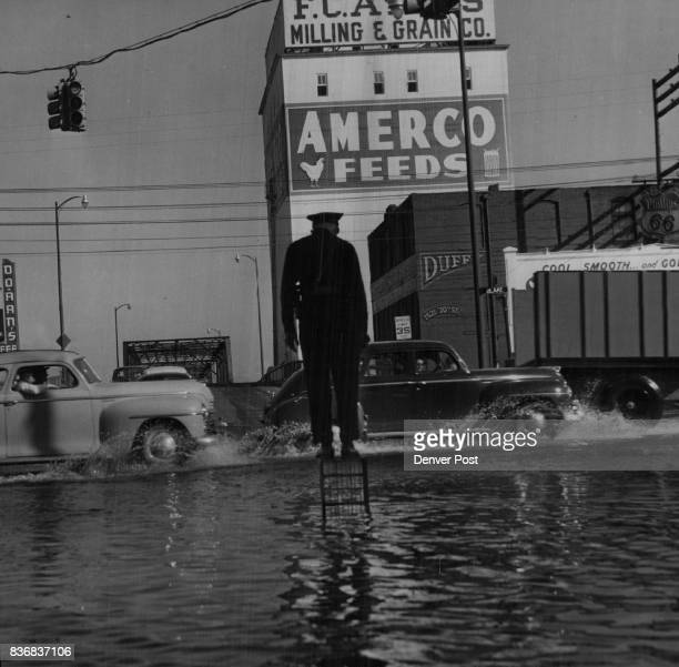 Floods Denver Patrolman A G Dill sought the sanctuary of an upended milk container case from which to direct motorists treading their way through...