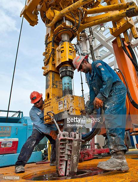 Floor hands Jose Garza left and Jose Salinas set slips to hold drilling pipe in the mouse hole on the Orion Perseus drilling rig near Encinal in Webb...