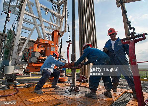 Floor hands Jose Garza left Jose Salinas center and Omar Cano make a pipe connection on Orion Drilling Co's Perseus drilling rig near Encinal in Webb...