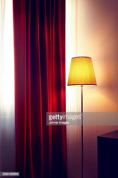 Floor lamp near red curtain