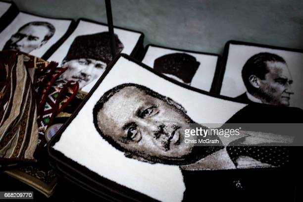 Floor mats printed with a portrait of Turkish President Recep Tayyip Erdogan are seen in front of carpets showing the portrait of the founder of...