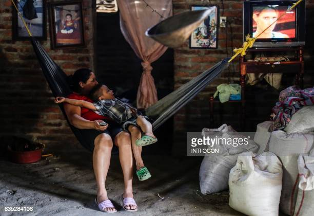 TOPSHOT Flor Rayos and her son watch television at their home in the Totumbla community in Dario Matagalpa some 90km from Managua on February 8 2017...