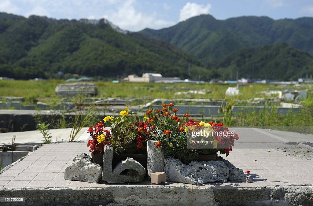 A floral offering stands on the base of a house swept away by the tsunami that followed last year's March 11 earthquake in Otsuchi Town, Iwate Prefecture, Japan, on Saturday, Sept. 8, 2012. Japan's economy expanded in the second quarter at half the pace the government initially estimated, underscoring the risk of a contraction as Europe's debt crisis caps exports. Photographer: Akio Kon/Bloomberg via Getty Images