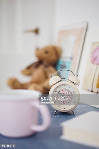 Floral pattern alarm clock on night table in girls room