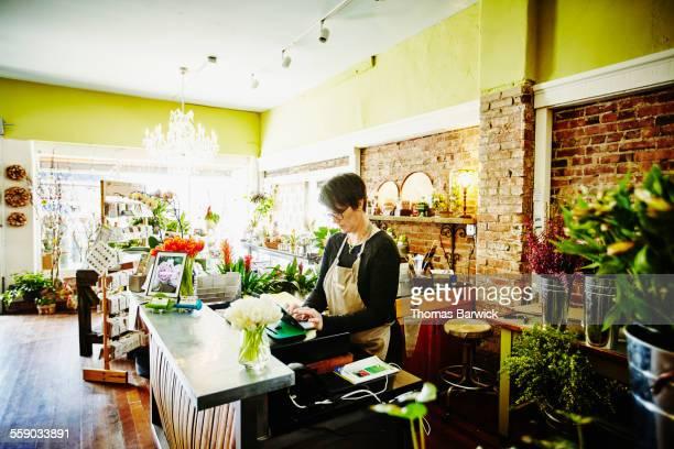 Floral shop owner working on digital tablet