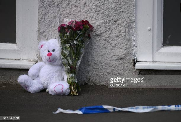 A floral tribute and a teddy bear are pictured alongside police tape near to the Manchester Arena in Manchester northwest England on May 23 2017...