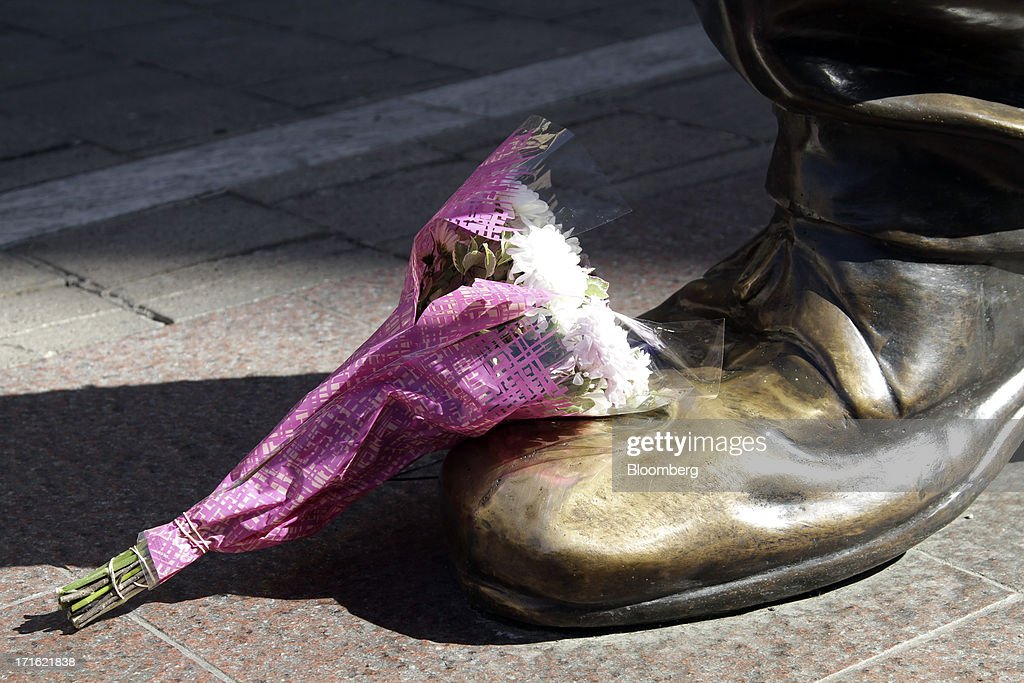 A floral tribute is placed on the foot of a giant statue to former South African president Nelson Mandela at Nelson Mandela square in Johannesburg, South Africa, on Thursday, June 27, 2013. South African President Jacob Zuma cancelled a trip to neighbouring Mozambique today after visiting Nelson Mandela, who remains critically ill in the hospital. Photographer: Nadine Hutton/Bloomberg via Getty Images