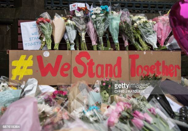 Floral tributes and a message that reads 'We Stand Together' are pictured in Albert Square in Manchester northwest England on May 24 left as tributes...