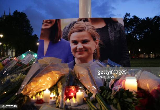 Floral tributes and candles are placed by a picture of slain Labour MP Jo Cox at a vigil in Parliament square in London on June 16 2016 Cox died...