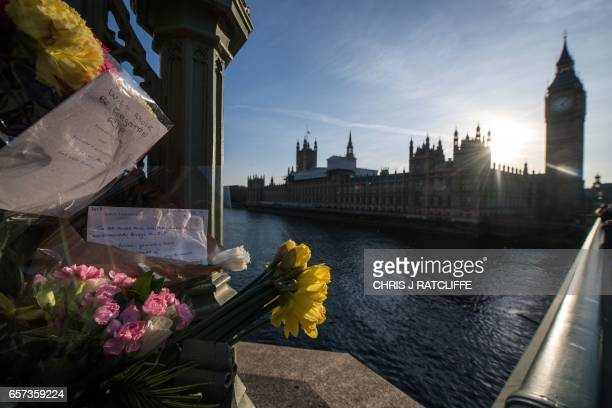 Floral tributes and messages of condolence are pictured on Westminster Bridge on the south side of the River Thames in front of the Houses of...