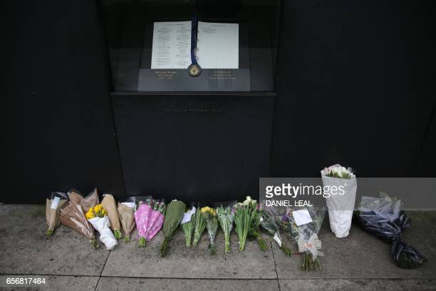 TOPSHOT Floral tributes are layed underneath the list of the fallen at the National Police Memorial in central London on March 23 2017 the day after...