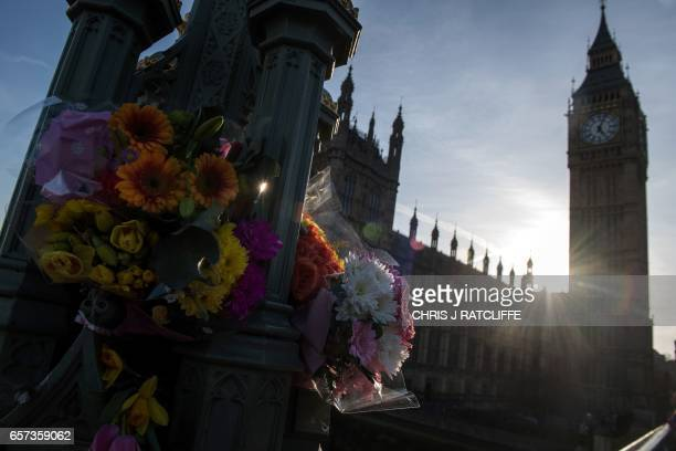 Floral tributes are pictured on Westminster Bridge in front of the Houses of Parliament in central London on March 24 2017 two days after the March...
