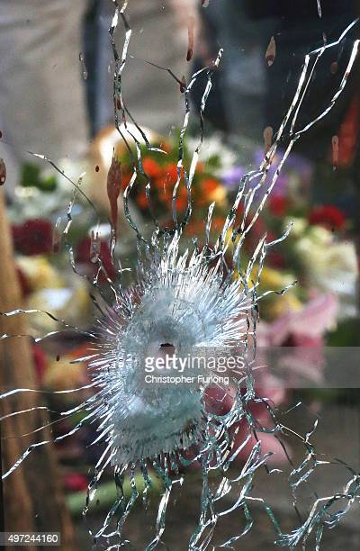Floral tributes are seen behind a bullet hole at Cafe Bonna Biere as France observes three days of national mourning on November 15 2015 in Paris...