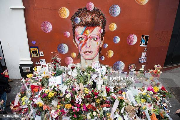 Floral tributes are seen beneath a mural of British singer David Bowie painted by Australian street artist James Cochran aka Jimmy C the day after...