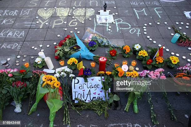 Floral tributes candles and chalked messages of condolence sit on Beursplein square in Brussels Belgium on Tuesday March 22 2016 Explosions ripped...