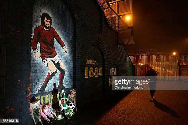 Floral tributes create a shrine in front of a mural for late soccer hero George Best at the entrance to Windsor Park football ground in Belfast on...