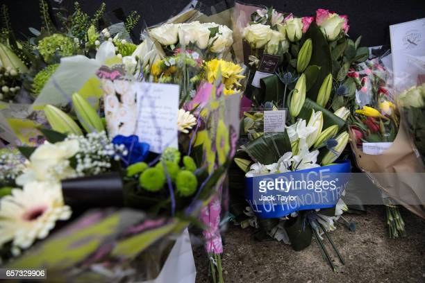 Floral tributes lay in front of the National Police Memorial on March 24 2017 in London England A fourth person has died after Khalid Masood drove a...