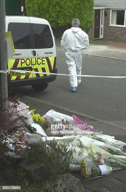 Floral tributes line the pavement as forensic experts continue their work outside the Mocherie family house in Rutland Close Barry Robert Mocherie...