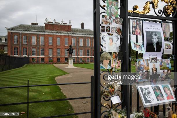 Floral tributes photographs and messages sit outside an entrance gate to Kensington Palace ahead of the 20th anniversary of the death of Diana...