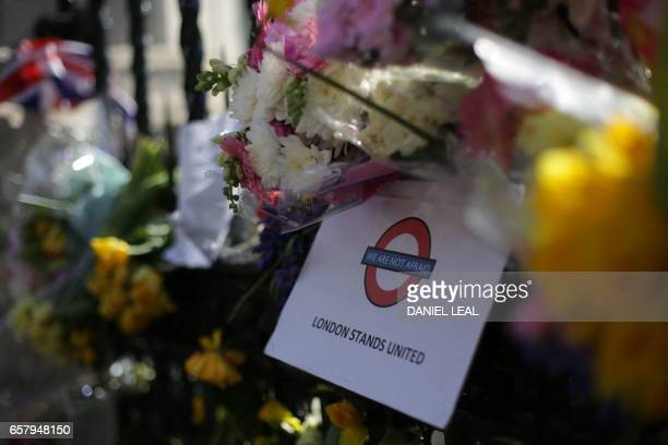 TOPSHOT Floral tributes to the victims of the March 22 terror attack and a message reading 'We are not afraid London stands united' are seen in...