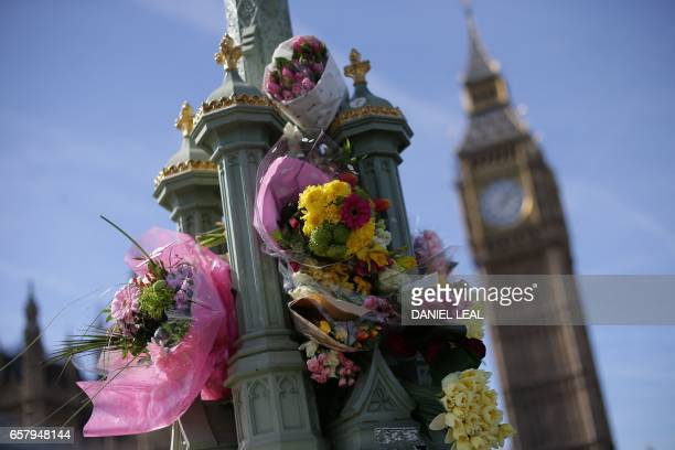 TOPSHOT Floral tributes to the victims of the March 22 terror attack are seen on Westminster Bridge near the Houses of Parliament in central London...