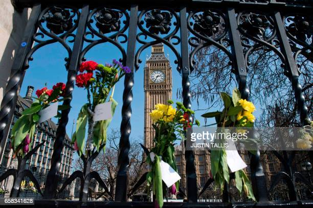 TOPSHOT Floral tributes to the victims of the March 22 terror attack are seen on outside the Houses of Parliament in Westminster central London on...