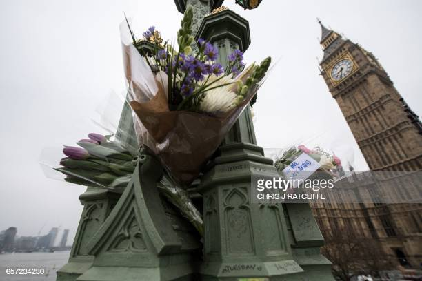 Floral tributes to the victims with a message reading 'we are not afraid' are seen on Westminster Bridge opposite the Houses of Parliament in central...