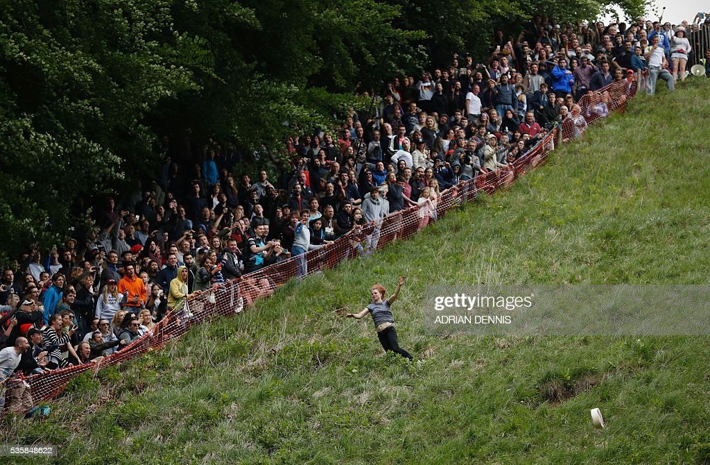 Florence Early chases the cheese on her way to winning the women's race ahead of her fellow competitors as they tumble down Cooper's Hill in pursuit of a round Double Gloucester cheese during the annual Cooper's Hill cheese rolling competition near the village of Brockworth, Gloucester, in western England, on May 30, 2016. The annual Cooper's Hill Cheese Rolling involves hordes of fearless competitors chasing an eight pound Double Gloucester cheese down a steep hill. The slope has a gradient in places of 1-in-2 and in others 1-in-1, its surface is very rough and uneven and it is almost impossible to remain on foot for the descent. The winner of the downhill race wins the cheese. / AFP / ADRIAN