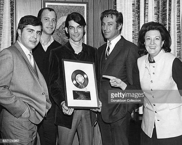 Florence Greenberg of Scepter Records presents BJ Thomas with a plaque commemorating a milestone in record sales as other record label executives...
