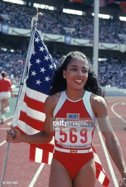 Florence Griffith Joyner of the USA walks with the American Flag as she celebrates setting a new Olympic record to win the gold medal in the Women's...
