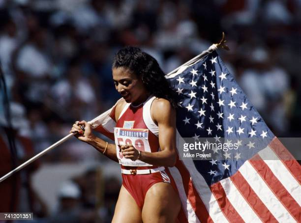 Florence GriffithJoyner carrying the Stars and Stripes flag of the United States celebrates winning gold in the Women's 100 metres final event during...