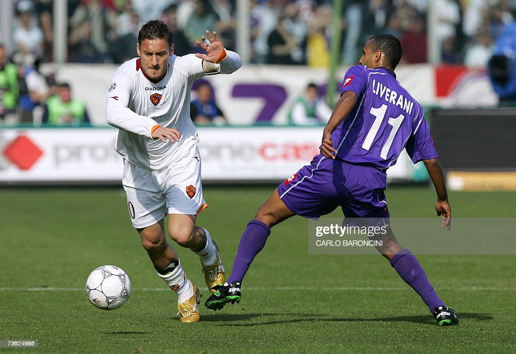 AS Roma's forward Francesco Totti is tackled by Fiorentina's midfielder Fabio Liverani during their Italian Serie A football match at Artemio Franchi...