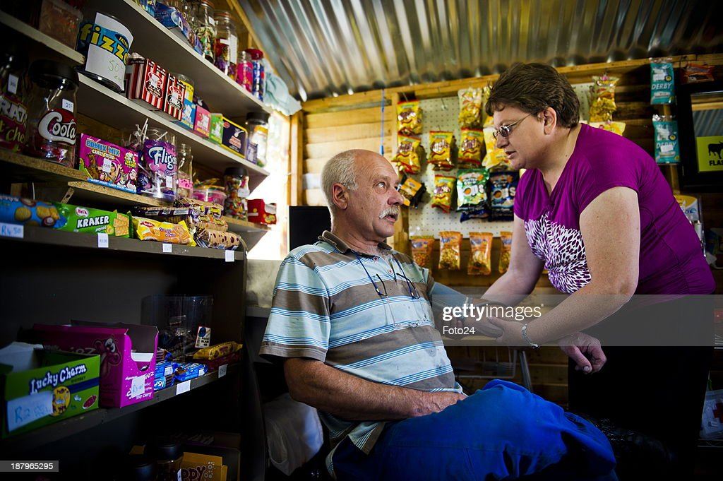 Florence van Niekerk takes Thinus Welthagens blood pressure at her spaza shop on November 12, 2013 in Kempton Park, South Africa. Van Niekerk started a small spaza shop in her backyard after she lost her job at a pharmacy. She sells airtime, bread, sweets and cigarettes and also takes customers blood pressure; tests for sugar and administers B12 injections. She is the only white person who recently completed a program for spaza shop owners presented by Wits Business School and Grand-Pa. A spaza shop is an informal convenience shop business in South Africa, usually run from home.