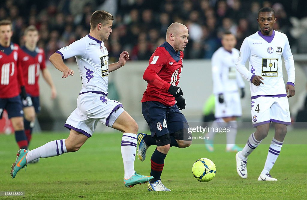 Florent Balmont of LOSC is followed by Franck Tabanou of Toulouse FC during the French Ligue 1 match between Lille OSC and Toulouse FC at the Grand Stade Lille Metropole on December 11, 2012 in Lille, France.