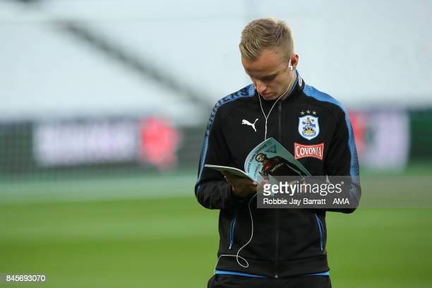 Florent Hadergjonaj of Huddersfield Town reads the match day programme prior to the Premier League match between West Ham United and Huddersfield...