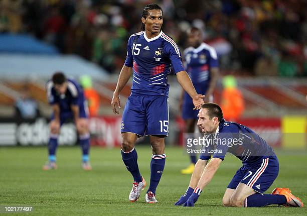 Florent Malouda of France helps up team mate Franck Ribery during the 2010 FIFA World Cup South Africa Group A match between France and Mexico at the...