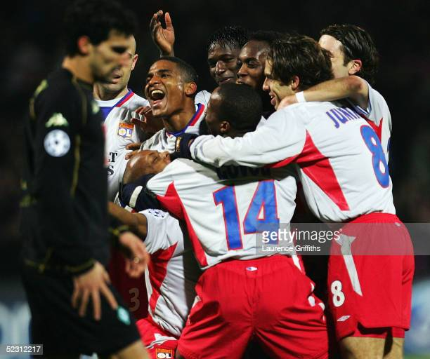 Florent Malouda of Lyon is mobbed after scoring as Paul Stalteri of Weder Bremen shows his dissapointment during the UEFA Champions League First...