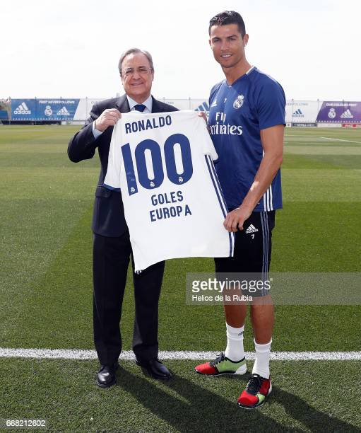 Florentino Perez presents Cristiano Ronaldo of Real Madrid with a commemorative shirt to mark his 100 European goals a training session at Valdebebas...