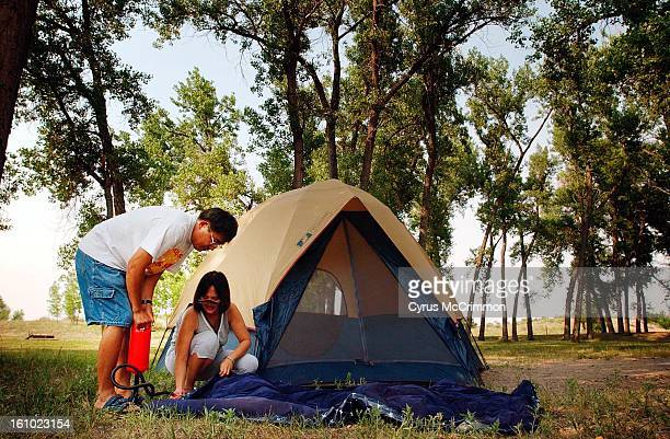 Florentino Singson and his wife Florisa Singson of Virginia work on inflating an air mattress for their tent while setting up camp at Cherry Creek...