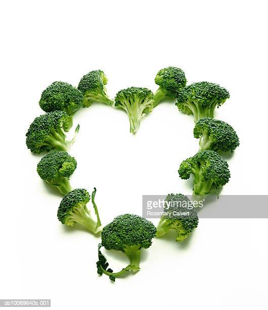 Florets of broccoli arranged in shape of heart, on white background