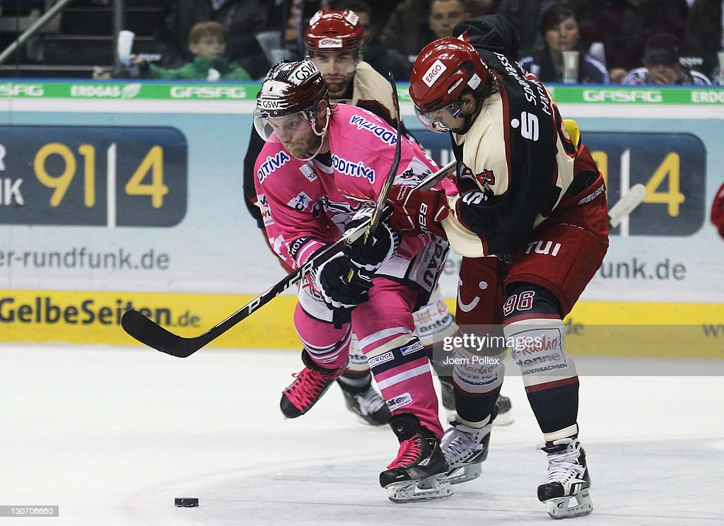 Florian Busch of Berlin and Andre Reiss of Hannover battle for the puck during the DEL Bundesliga match between EHC Eisbaeren Berlin and Koelner Haie...