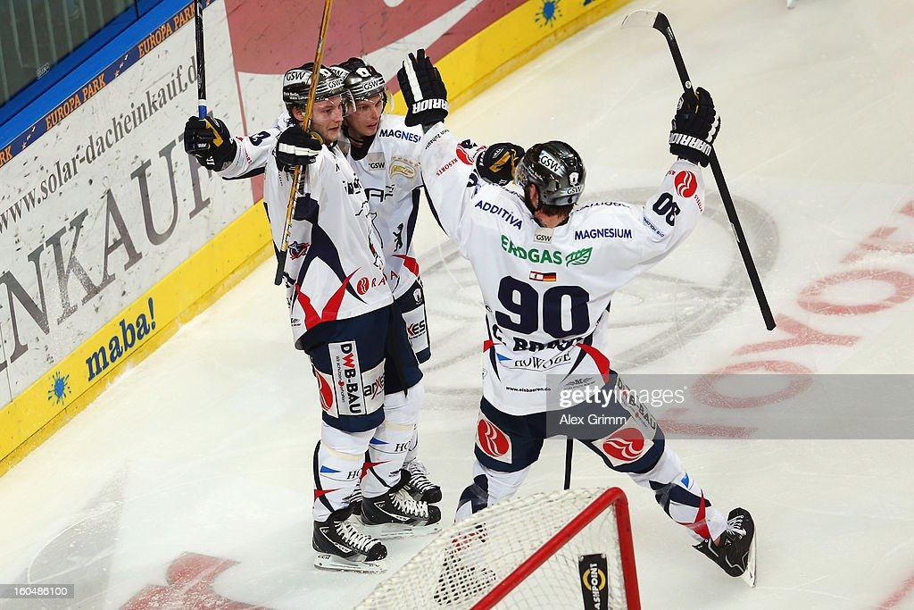 Florian Busch (L) of Berlin celebrates his team's fourth goal with team mates during the DEL match between Adler Mannheim and Eisbaeren Berlin at SAP Arena on February 1, 2013 in Mannheim, Germany.
