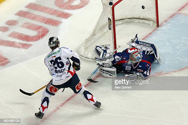 Florian Busch of Berlin scores his team's fourth goal against goalkeeper Dennis Endras of Mannheim during the DEL match between Adler Mannheim and...