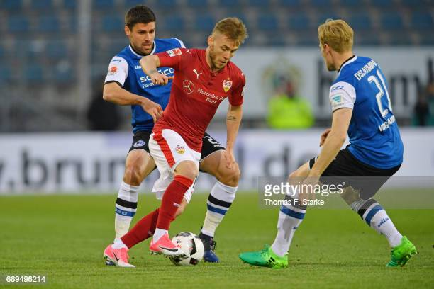 Florian Dick and Andreas Voglsammer of Bielefeld tackle Alexandru Maxim of Stuttgart during the Second Bundesliga match between DSC Arminia Bielefeld...
