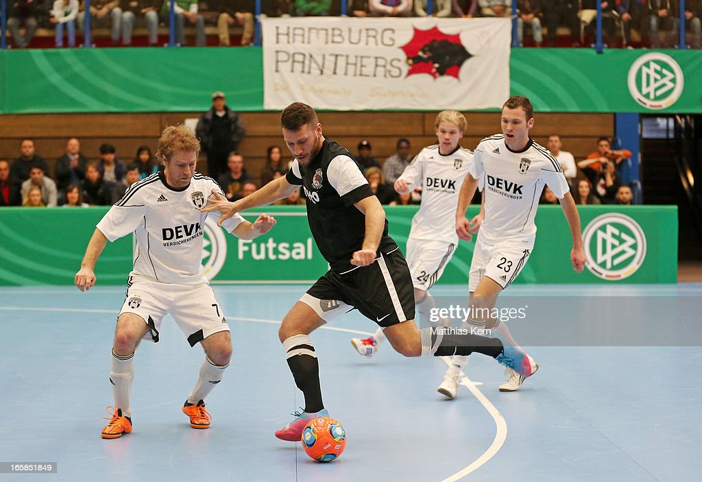 Florian Dondorf (L) of Muenster battles for the ball with Erdinc Oruen (C) of Hamburg during the DFB Futsal Cup final match between Hamburg Panthers and UFC Muenster at Sporthalle Wandsbek on April 6, 2013 in Hamburg, Germany.